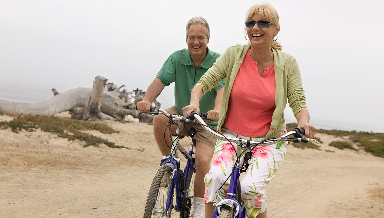 Couple-cycling-on-beach_1232x700